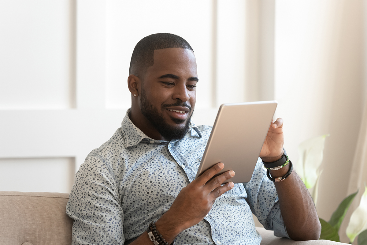 Smiling young african man using digital tablet at home, millennial black male user holding computer looking at screen reading e-book app online relaxing on leisure with device work study sit on sofa